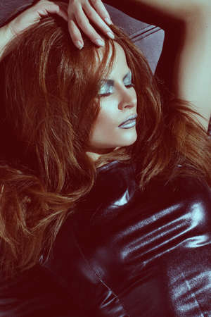 girl with red hair in a leather dress