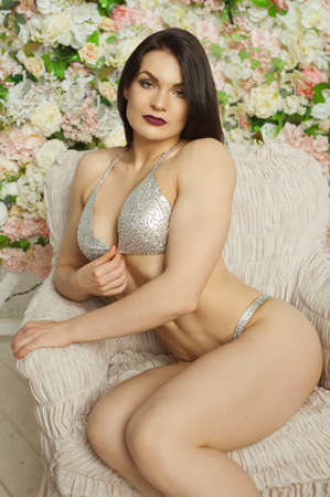 pastes: fitness girl in a silvery bathing suit with pastes, sits in a chair, against a set of flowers