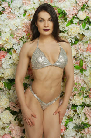 pastes: athletic girl in a silvery bathing suit with pastes, costs against flowers Stock Photo