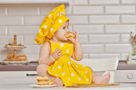 eats: girl the child in a yellow suit of the cook,sits on a kitchen table, eats croissant