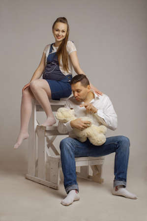 awaiting: pregnant wife with the husband who holds Teddybear,sit on steps in studio