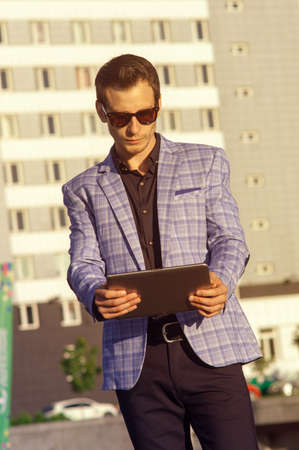 Businessman in sunglasses with a tablet in hands,dressed in a suit with a checkered jacket
