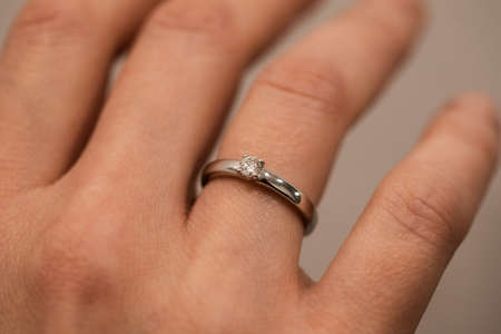 woman is wearing golden ring with diamond