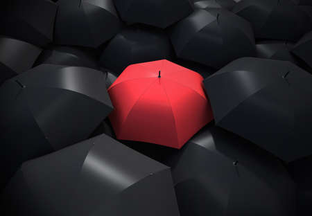 Red umbrella standing out from background of black umbrellas photo