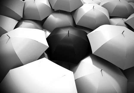 exceptional: Black umbrella standing out from background of white umbrellas Stock Photo