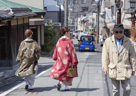 Unidentified woman dressed in kimono walking on street