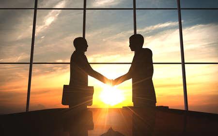 2 つのビジネス オフィスのシルエットで握手