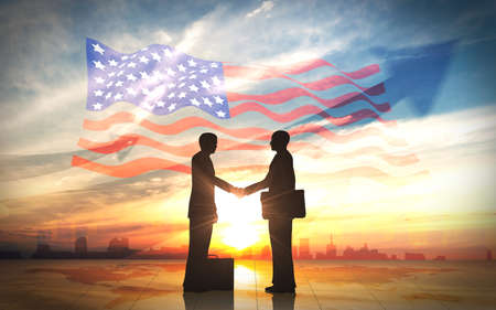 Two business man shake hand silhouettes city with american flag Stock Photo