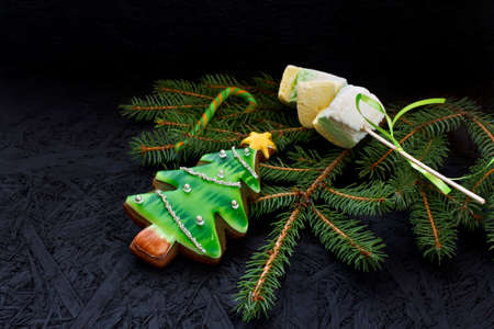 Gingerbread and marshmallows on spruce branches laid out on a black background. View from above. New Year's and Christmas.