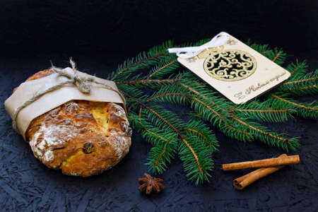 Traditional German Christmas pastry - stollen on a black background with fir branches, spices and Christmas decorations.