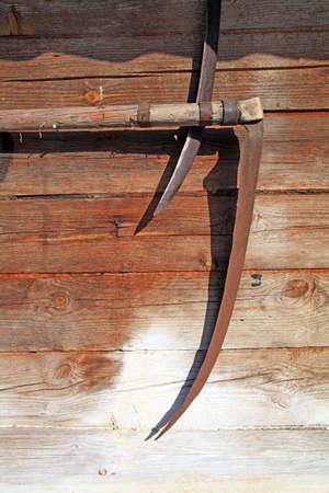 scythe: aging scythe on wall