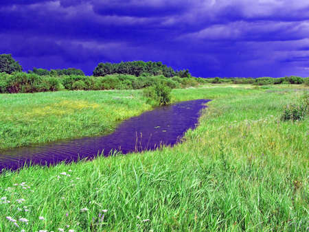 small river on field before thunderstorm photo