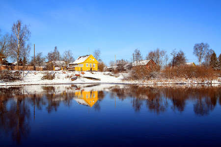 reflection yellow house in river photo