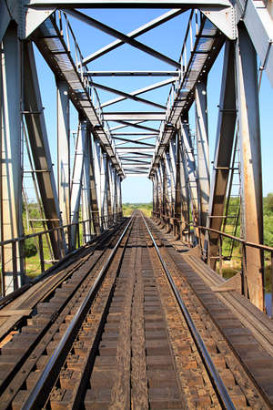 railway bridge through small river photo