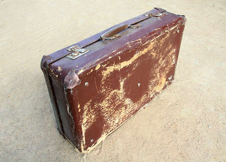 valise: old valise on yellow sand
