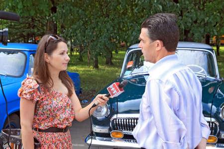 Staraja Russa, Russia - 9 luglio: Uomo sconosciuto intervistato da corresponder della televisione russa su annuale festival retr� automobili in Staraja Russa, Russia in 9 luglio 2011.