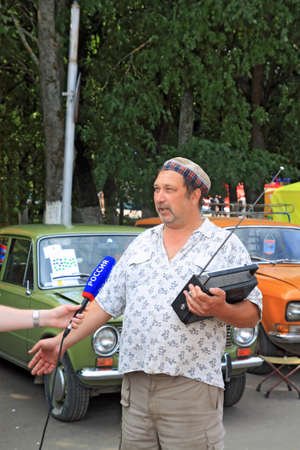 interviewed: Staraja Russa, Russia - July 9: Unknown man interviewed by corresponder of the Russian television on annual festival retro cars in Staraja Russa, Russia in July 9, 2011.  Editorial