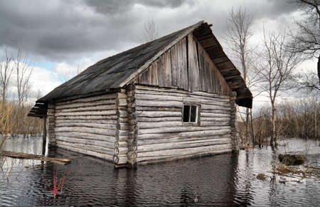 storm damage: old rural house in water