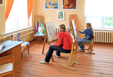 two girls draw in studio