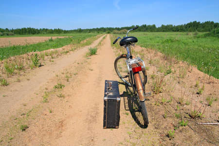 valise: old valise near old bicycle on rural road