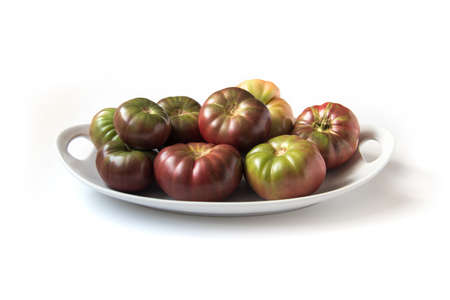 Organic heirloom Brandywine tomatoes on a plate, isolated on white