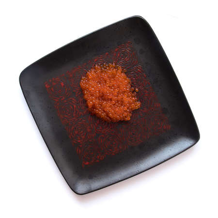 Red salmon caviar on a black square plate, isolated on white, top view Stock Photo