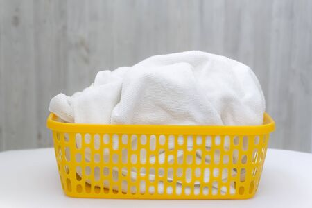 White clean towel in a yellow plastic laundry basket on a gray wall background. Laundry, home cleaning, cleanliness