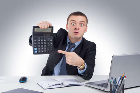unhappy man: Very angry businessman in office, holding a calculator on gray background