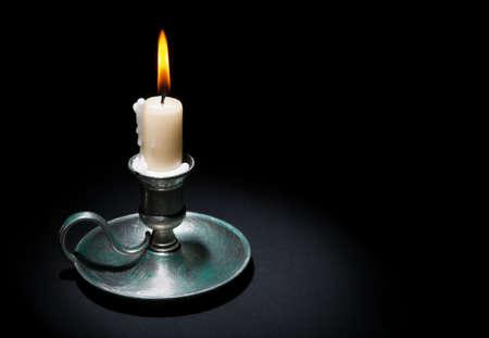 Brandende kaars in een oude tinkandelaar op een zwarte achtergrond