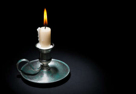 holder: Lighted candle in an old tin candlestick on a black  background