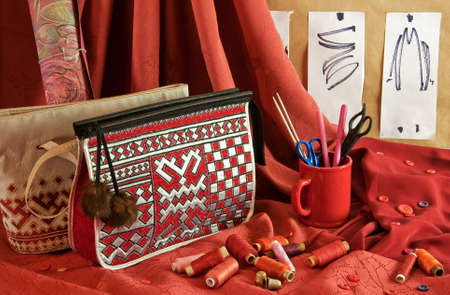 fashion sketches, handbags, red fabric, buttons and thread photo