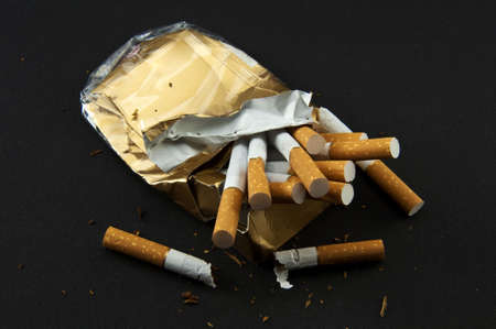 Stop Smoking! Broken crushed pack of cigarettes on the black background.