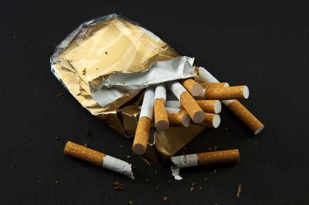 cigarette filter: Stop Smoking! Broken crushed pack of cigarettes on the black background.