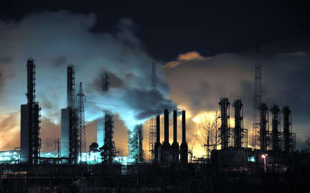 A brightly lit industrial site at night with plumes of smoke coming from chimneys.  Russia, Western Siberia.