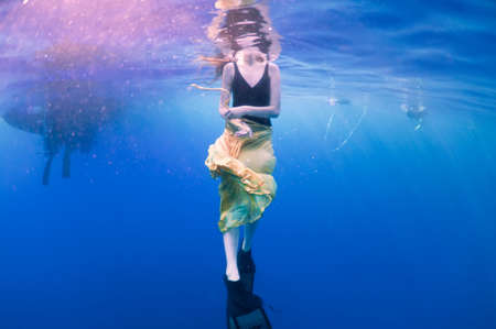 underwater woman: girl in a yellow skirt and its reflection on surface of the sea, underwater view.