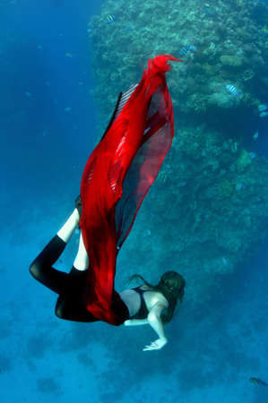 young girl in red pareo dives into depths on background of coral reef photo