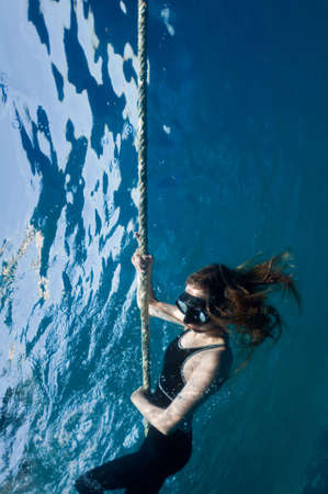 freediver girl in the depths of the turquoise sea photo