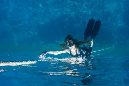 snorkeling girl lies on the surface of water. underwater inverted form. photo