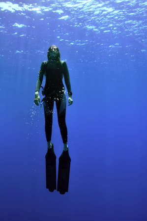 young girl with long fins rise from the deep of sea to the surface and sun