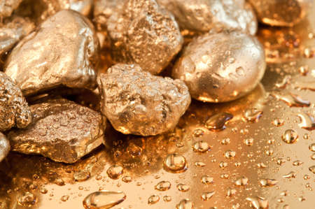 shiny gold nuggets and water drop background. closeup. Stock Photo