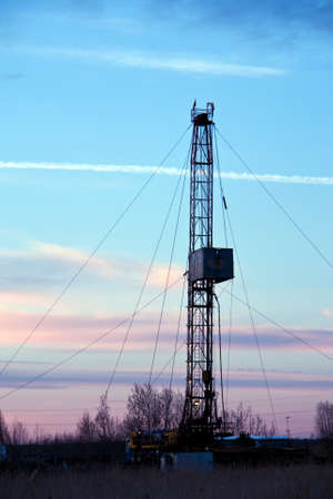 Vertical view of a drilling rig on a sunset background photo