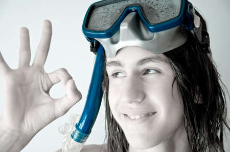 attractive teenager with long wet hair, wearing a diving mask, showing ok. monochrome. photo