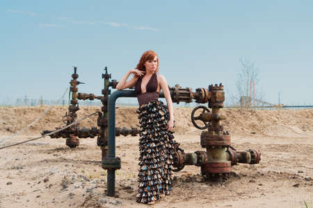 red-haired woman in a long dress on the oil well background  photo