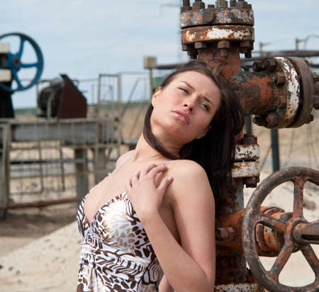 jack pump: beautiful young brunette woman on the oil field Stock Photo
