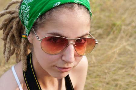 mujer hippie: mujer joven hippie en un pa�uelo verde y gafas de sol