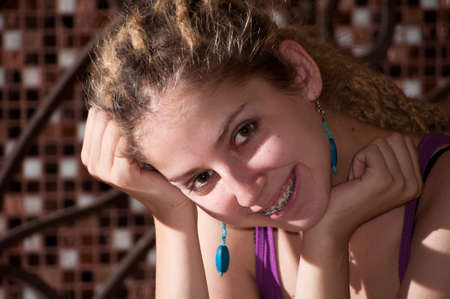 portrait of a young girl with dreadlocks on the background of a decorative mosaic. big eyes. blue earrings. photo