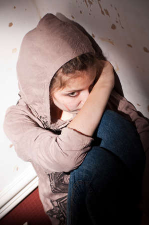 teenage problems. lonely, unhappy, sad girl sitting on the floor  in a dark corner  dirty room. Stock Photo - 7628613