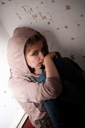 teenage problems. lonely, unhappy, sad girl sitting on the floor  in a dark corner  dirty room. Stock Photo - 7628616