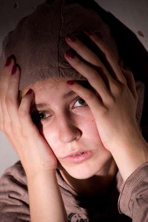 teenage problems: problemas de los adolescentes. Retrato de una chica solitaria, infeliz, triste. en gris, sostiene su cabeza con las manos
