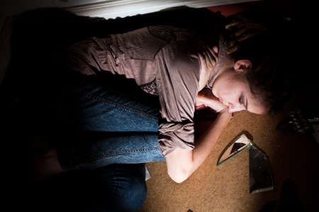 teenage problems: problemas de los adolescentes. chica solitaria, infeliz, triste acostado en el piso sucio en una habitaci�n oscura. Disco dura luz selectiva.